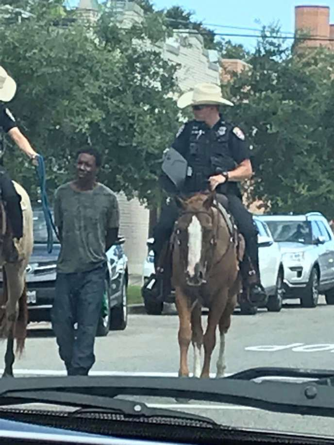 On the streets of Galveston, Texas, two white policemen on horseback pull a black suspect by a rope