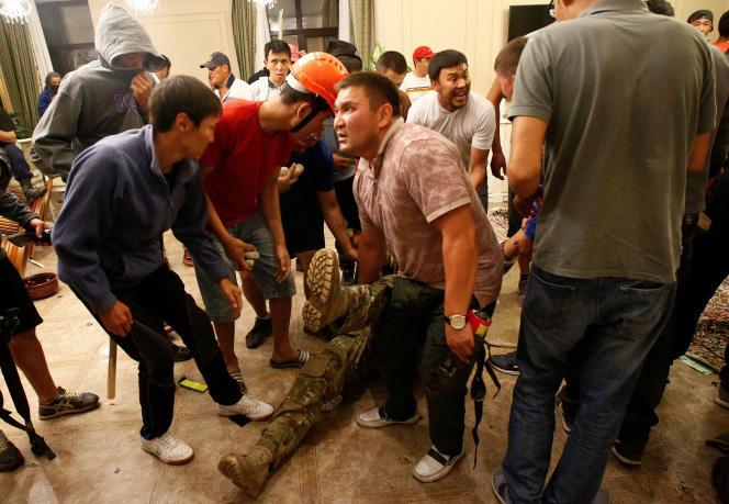 Des partisans armés d'Almazbek Atambaïev entourent un membre blessé des forces spécialesfait prisonnier à l'intérieur de la résidence de l'ancien chef d'Etat, à Koï-Tach le 7août2019.