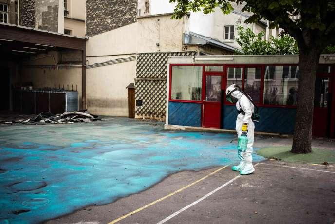 Un ouvrier réalise les travaux de décontamination des cours du groupe scolaire Saint-Benoît, dans le 6earrondissement de Paris, le 8 août.