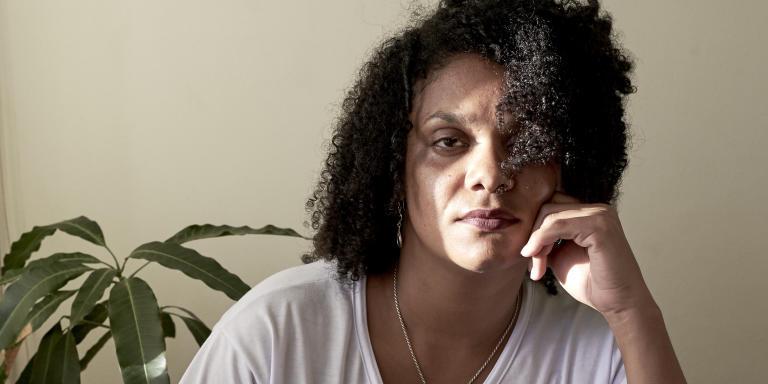 Ludmilla Teixeira, activiste noire antibolsonaro, initiatrice du mouvement #EleNão. Diplômée en communication et fonctionnaire publique, la féministe pose dans son appartement situé dans l'état de Bahia, le 1 juillet 2019. Elle a commencé son combat Antibolsonaro en rasemblant les brésiliennes, via les résaux sociaux «Mulheres unidas contra Bolsonaro» qui compte aujourd'hui plus de 9.5k membres. Elle porte un tee-shirt avec le logo du mouvement dont elle est à l'origine, et une phrase de la féministe et défenseuse des droits de l'homme Marielle Franco, assasinée le 14 Mai 2018 à la suite d'un post twitter