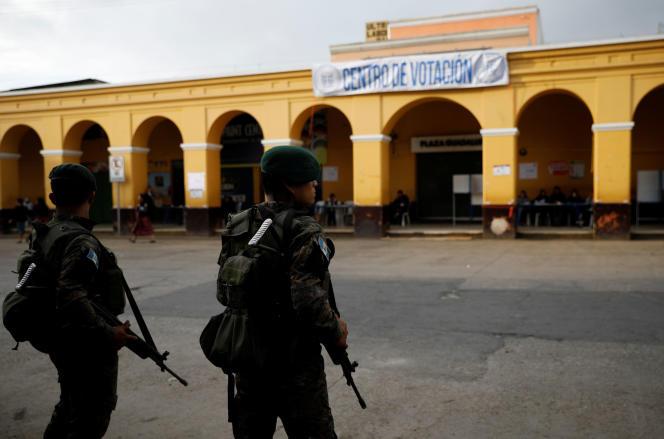 Des militaires montent la garde devant un bureau de vote à San Juan Sacatepequez, au Guatemala, dimanche 11 août.