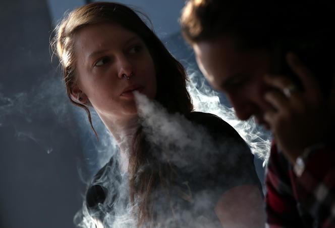 Une jeune femme fume une cigarette électronique à San Rafael, en Californie. En2018, un lycéen américain sur cinq vapotait.