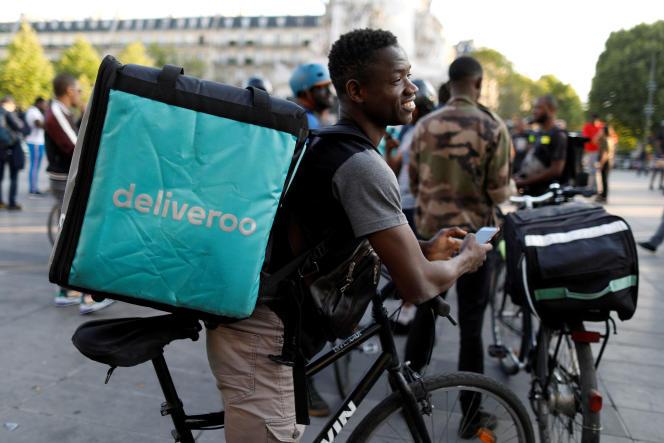 Un livreur Deliveroo manifeste place de la République, à Paris, contre la réduction du prix de la course à Paris, le 7 août 2019.