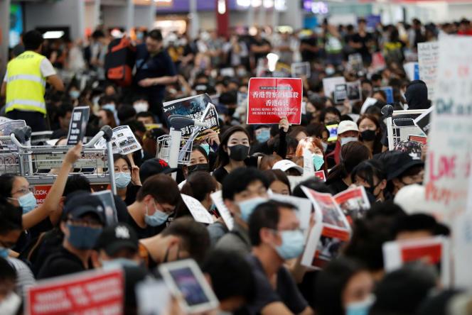 Des manifestants antigouvernementaux sont assis par terre devant les barrières de sécurité lors d'une manifestation à l'aéroport de Hongkong, en Chine, le 13 août 2019.