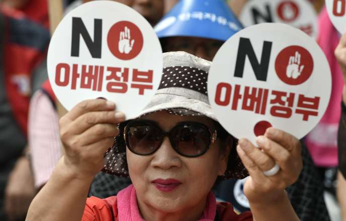 Une manifestante sud-coréenne brandit des pancartes portant la mention «Le gouvernement de M. Abe» lors d'un rassemblement anti-japonais dans le centre de Séoul le 13 août.
