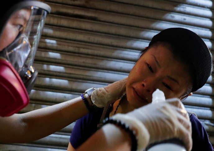 Une femme affectée par des gaz lacrymogènes, à Hongkong, le 14 août.