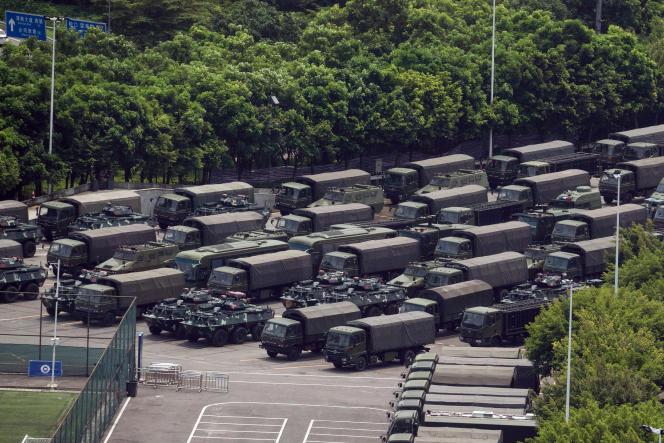 Camions militaires et véhicules blindés devant un stade de football à Shenzhen.