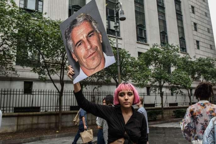 Une femme demande que la justice poursuive son enquête sur le milliardaire, son portrait en main, devant le palais de justice le 8 juillet, à New York.