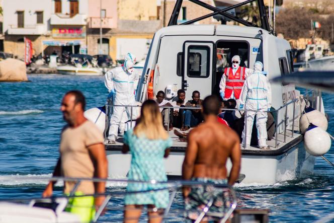 Des migrants mineurs non accompagnés sont escortés depuis le navire «Open-Arms» jusqu'à Lampedusa, en Italie, le 17 août.