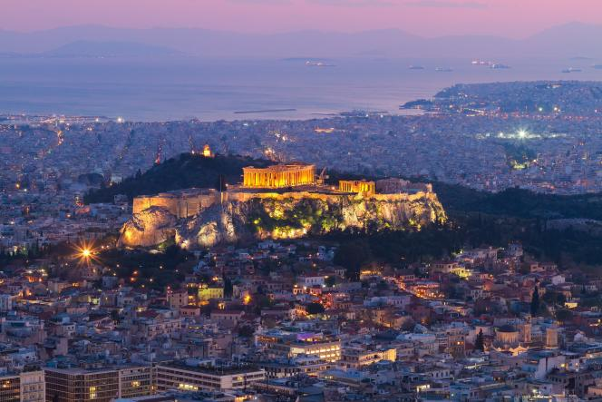 A Athènes, il est encore possible d'acheter un studio pour le louer à partir de 30 000 euros, voire 20 000 euros. Coucher de soleil sur Athènes avec l'Acropole illuminé.
