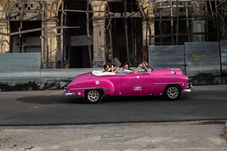An American old car rolls with tourists in front of an old building in Old Havana, Cuba,  July 8, 2019.