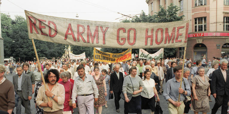 Pro-democracy supporters holding banner asking for the withdraw of Red Army from Lithuania march 22 June 1991 in Vilnius commemorating the 50the anniversary of the Lithuanian uprising against the Red Army and Stalin' regime. Three weeks after the tiny Lithuania unilaterally declared its independence from Moscow, 31 March 1990 the Soviet army has intervened by rounding up deserters and seized control of the Communist Party headquarters in Vilnius. (Photo by VIRGIS USINAVICHIUS / AFP)