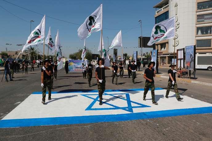 Des membres de la Mobilisation populaire, un réseau de milices chiites, marchent sur un drapeau israélien, à Bagdad, le 31 mai.
