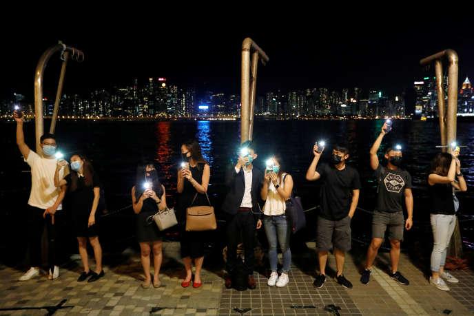 Des manifestants hongkongais allument leur téléphone portable en formant une chaîne humaine, vendredi 23 août, en hommage à celle qui trente ans plus tôt avait réuni près de deux millions de personnes dans les pays baltes pour réclamer l'indépendance.