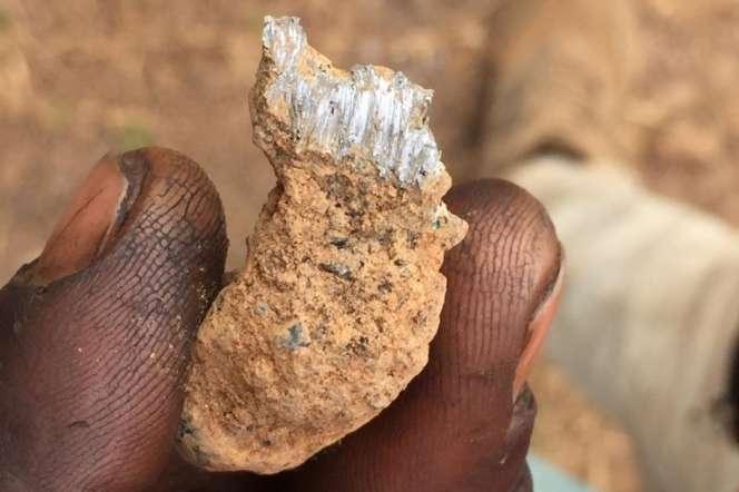 Un homme travaillant à la décharge de déchets miniers de Kabwe montre un morceau de roche, en 2018.