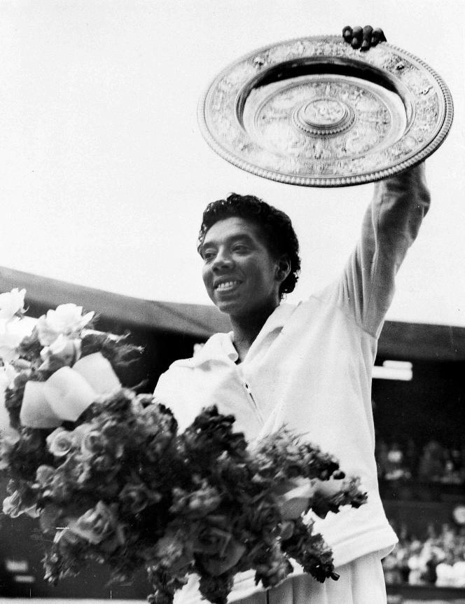 Althea Gibson soulève son trophée après sa deuxième victoire en finale du tournoi de Wimbledon contre la joueuse britannique Angela Mortimer, le 5juillet1958.