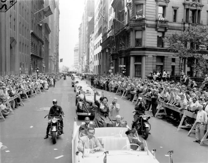 Le 11 juillet 1957, Althea Gibson revient triomphale à New York après avoir remporté la compétition féminine de Wimbledon. Elle sourit et salue ici a foule lors d'un défilé grandiose en son honneur, à Broadway.