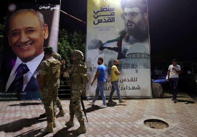 Des militaire libanais devant une affiche deHassan Nasrallah, chef de file duHezbollah, le 28 août près de la frontière israélienne.