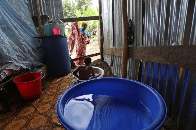 Une femme donne le bain à son fils dans une maison en tôle à Mamoudzou, à Mayotte en 2013.