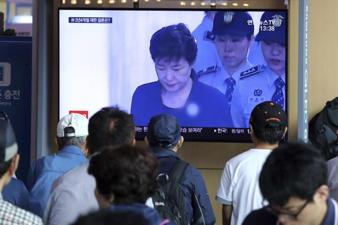 jeudi 29 août 2019,à la gare ferroviaire de Séoul, en Corée du Sud, les passants regardent les dernières informations au journal télévisé concernant l'ex-présidente Park Geun-hye.