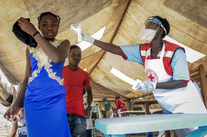 La température des personnes en provenance de RDC est mesurée pour dépister les symptômes d'Ebola, au poste frontalier de Mpondwe avec le Congo, à l'ouest de l'Ouganda, le 14 juin 2019.