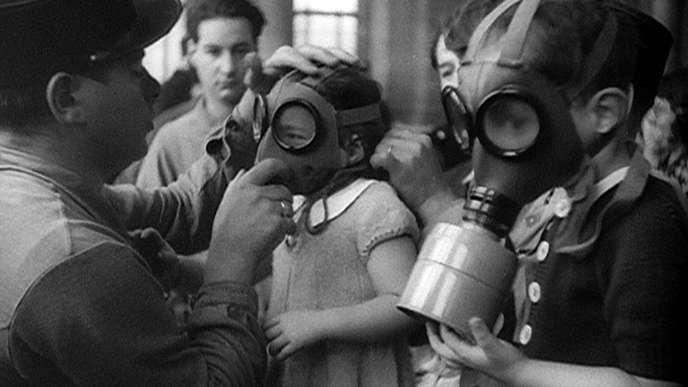 Essayage de masques à gaz pour enfants au début de la seconde guerre mondiale.