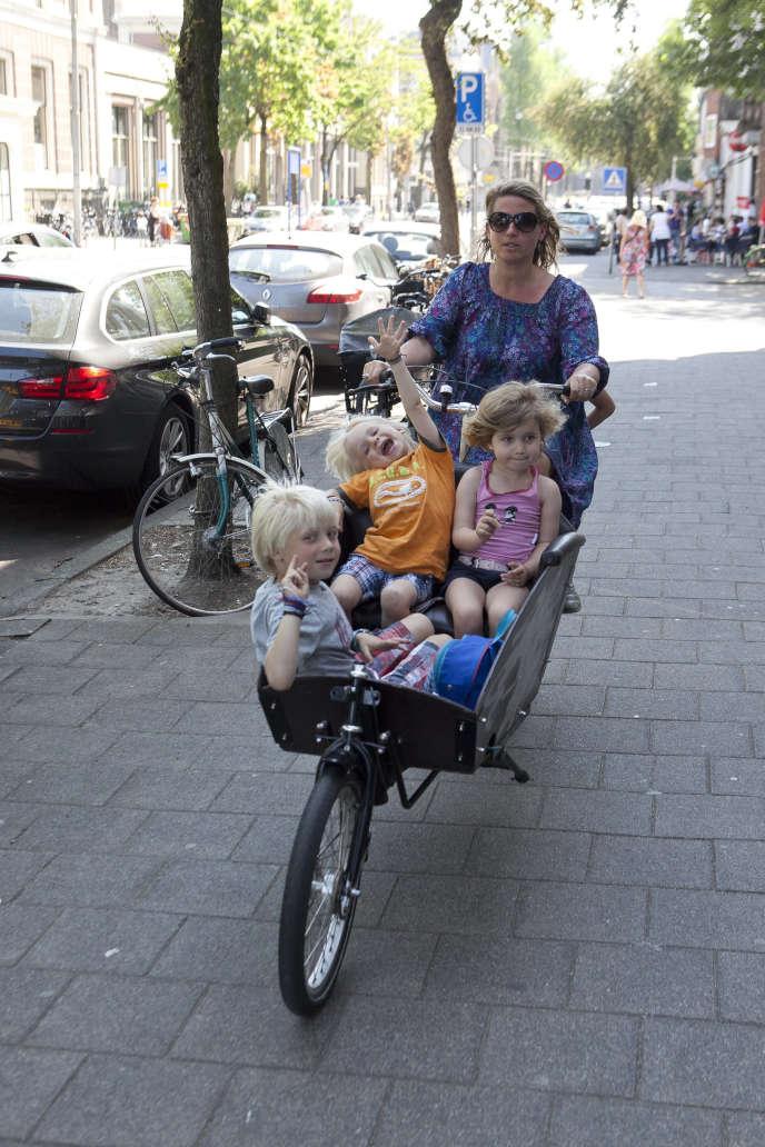 Une«bakfietsmoeders», ou« mère à vélo-cargo», avec ses enfants dans une rue d'Amsterdam, en 2012.