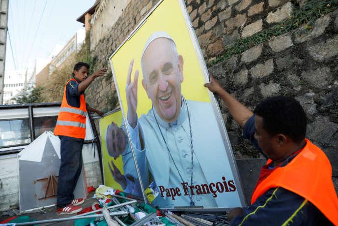 Les autorités municipales accrochent un portrait du pape François à Antananarivo le 27 août 2019.