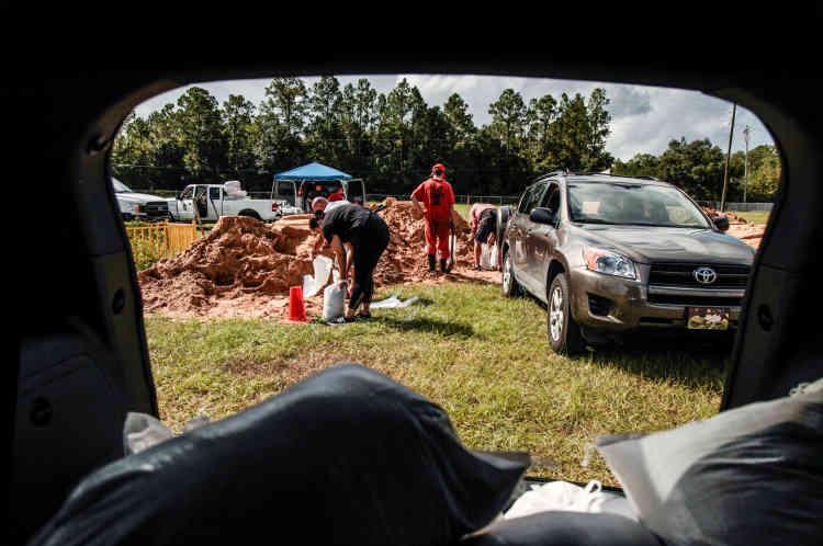 Des habitants de Middleburg, aidés par des détenus, remplissent des sacs de sable pour protéger leurs maisons des vents violents et des pluies qui accompagnent l'ouragan.