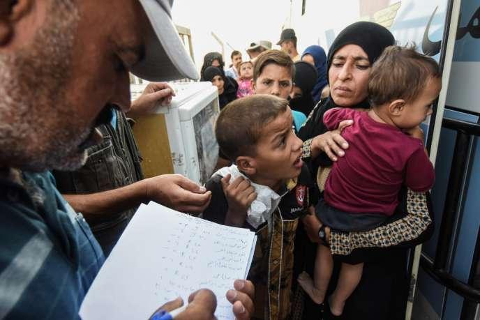 A Hammam Al-Alil, en août 2019. Des Irakiens déplacés se préparent à embarquer à bord d'un bus vers la province de Kirkouk.