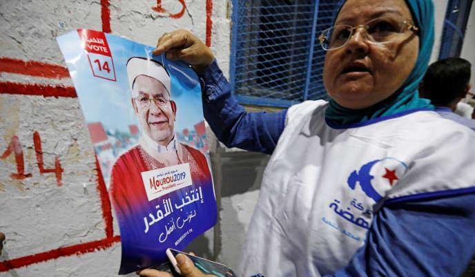 Une militante colle l'affiche de campagne du candidat d'Ennahda, Abdelfattah Mourou, à Tunis, le 2 septembre.