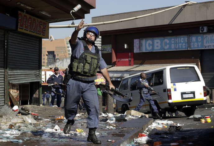 Un officier de police lançant une grenade lacrymogène, mardi 3 septembre à Germiston, un quartier de l'est de Johannesburg (Afrique du Sud).