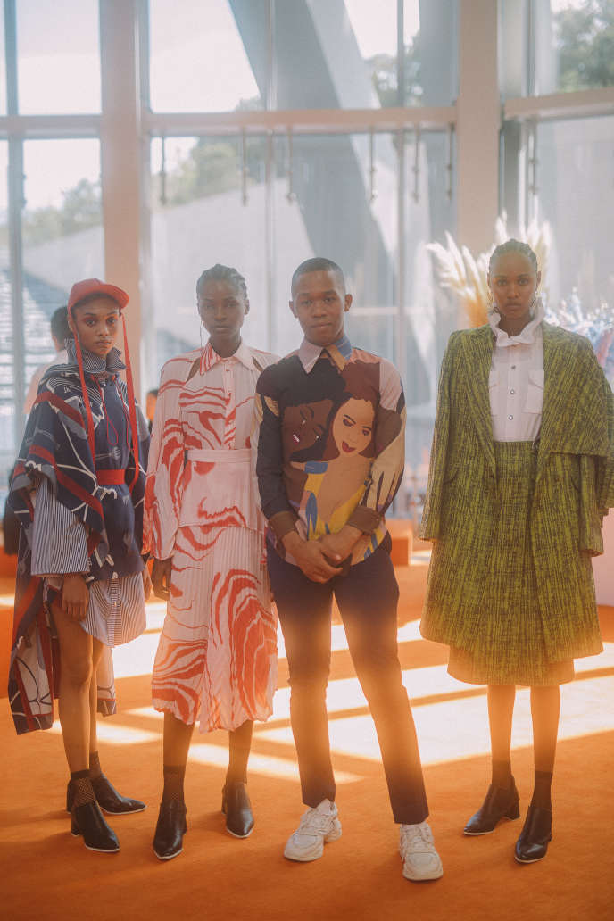 Le Sud-Africain Thebe Magugu entouré de trois mannequins portant ses créations.