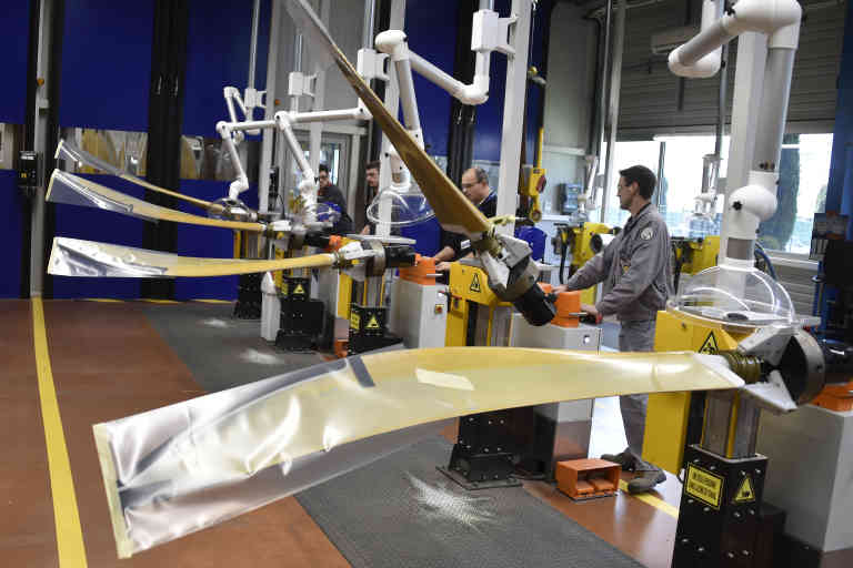This picture taken on March 14, 2017 shows four Ratier-Figeac employees working on propellers for Avions de Transport Regional (ATR) at the Figeac factory. - The company Ratier-Figeac is the worldwide leader for cockpit and cabin equipment for civillian turbo-jets, especially for Avions de Transport Regional (ATR), Bombardier, European Aeronautic Defence and Space (EADS), Construcciones Aeronáuticas Sociedad Anónima (CASA) and Xian Aircraft Corporation(XAC) and for military applications with the most advanced and most used by the E2 of the US Navy and the A400M of Airbus Defense & Space, 8 blades composite propellers. (Photo by PASCAL PAVANI / AFP)
