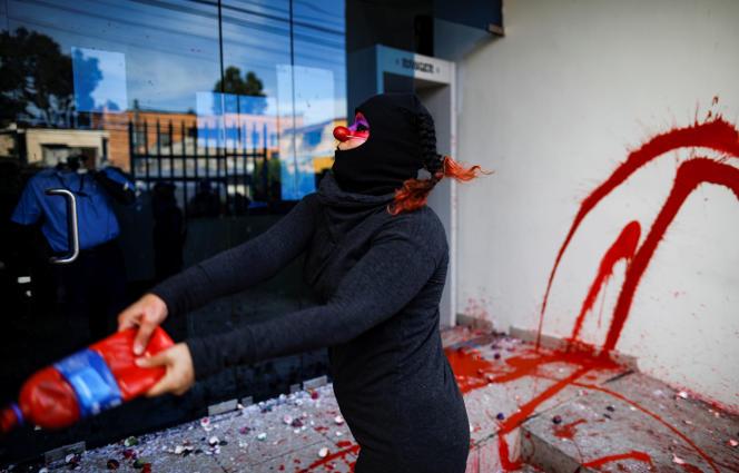 San Salvador, le 9 septembre. Une militante féministerépand de la peinture rouge à l'entrée du siège du parquet pour dénoncer un acharnement judiciaire contre Evelyn Hernandez.REUTERS/Jose Cabezas