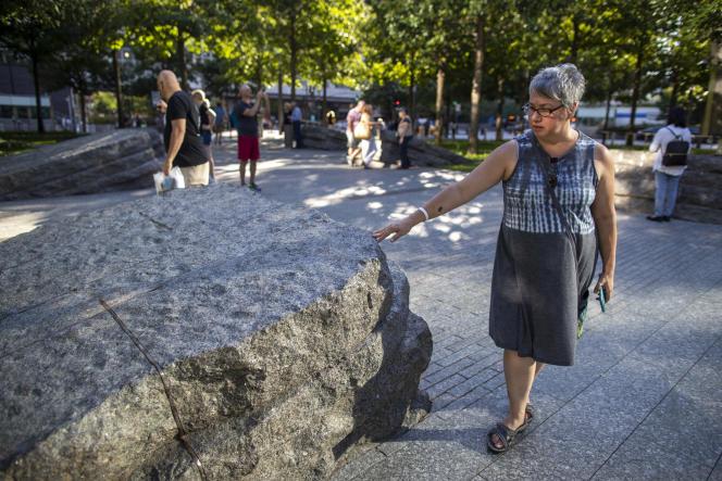 Une femme touche l'un des rochers installés en mémoire des victimes collatérales de l'attentat de 2001, le 29août.