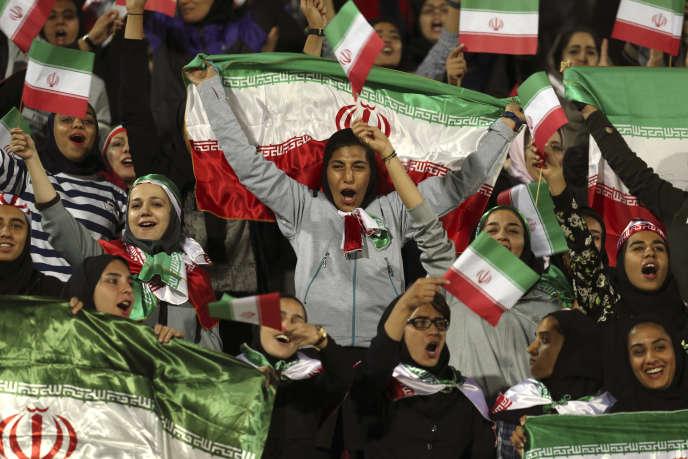 Sur cette photo datée du 16 octobre 2018, des femmes iraniennes applaudissent enagitant le drapeau de leur pays après que les autorités ont, dans un geste rare, permis à un groupe choisi de femmes d'entrer dans le stade Azadi pour regarder un match amical de football entre l'Iran et la Bolivie, à Téhéran.