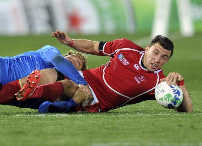 Le Russe Vasily Artemyev se fait plaquer par un joueur italien lors d'un match de poule de la Coupe du monde en 2011.