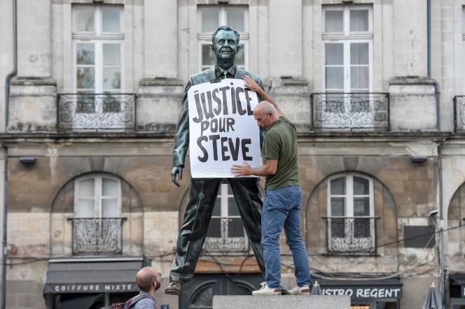Un homme fixe une affiche sur une statue, à Nantes, le 12 septembre 2019, lors d'un rassemblement en hommage à Steve Maia Canico
