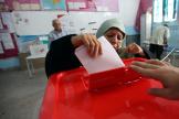 Une femme met son bulletin de vote dans l'urne, le 15 septembre, jour de la présidentielle