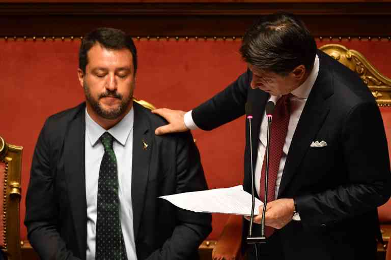TOPSHOT - Italian Prime Minister Giuseppe Conte (R) touches Deputy Prime Minister and Interior Minister Matteo Salvini's shoulder as he delivers a speech at the Italian Senate, in Rome, on August 20, 2019, as the country faces a political crisis. Italy's Premier Conte says to offer resignation during his speech at the Senate after calling Italy's far-right Interior Minister Matteo Salvini