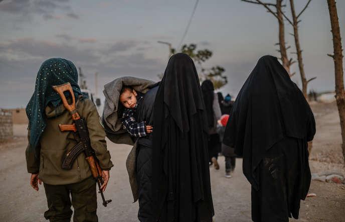 Des femmes voilées escortées par une combattante des Forces démocratiques syriennes, dans le camp d'Al-Hol, le 17 février.
