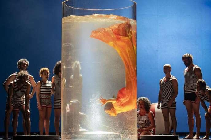 Une femme méduse aux voiles orangés dans un bocal empli d'eau, «Einstein on the Beach» mis en scène par Daniele Finzi Pasca.