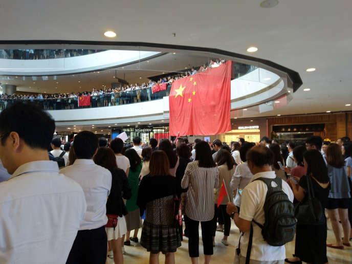 Dans la galerie marchande de l'IFC à Hongkong, face à des manifestants antigouvernementaux des pro-Chinois déroulent de grands drapeaux, des différents balcons surplombant l'un des atriums du centre commercial, le 12 septembre.