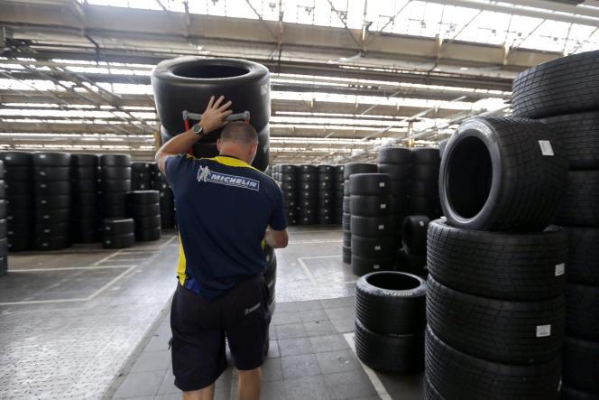Un ouvrier pousse un chariot avec des pneus de sport automobile, dans l'usine Michelin à Clermont-Ferrand, le 10 juillet 2013.