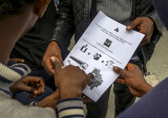 A Calais, en août 2016, des migrants en provenance d'Erythrée, en Afrique de l'Est, lisent le document d'information, formulé en tigréen, sur la procédure de demande d'asile.