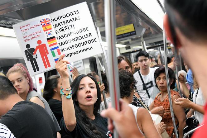 Des citoyens barcelonais alertent les passagers du métro contre les pickpockets, en août.