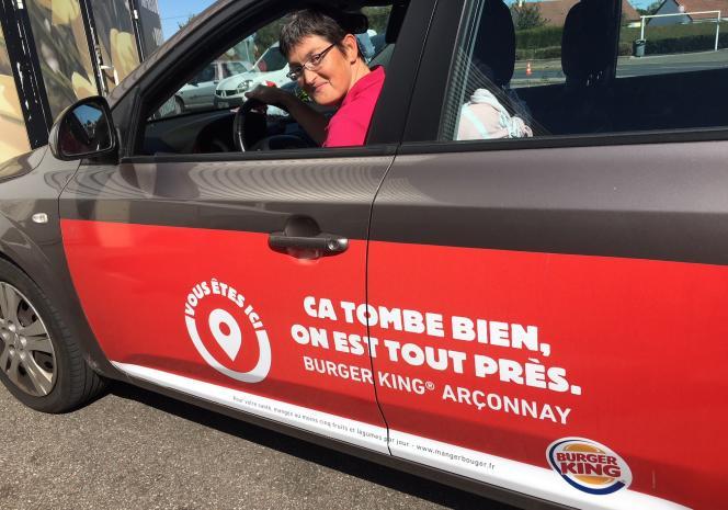 Isabelle, au volant de sa KIA Ceed, ornée d'un message publicitaire pour le Burger King d'Arçonnay, juste à côté d'Alençon.