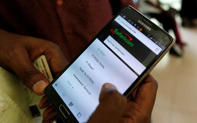 Un usager installe le service de transfert d'argent M-Pesa sur son smartphone, à Nairobi, le 11mai 2016.
