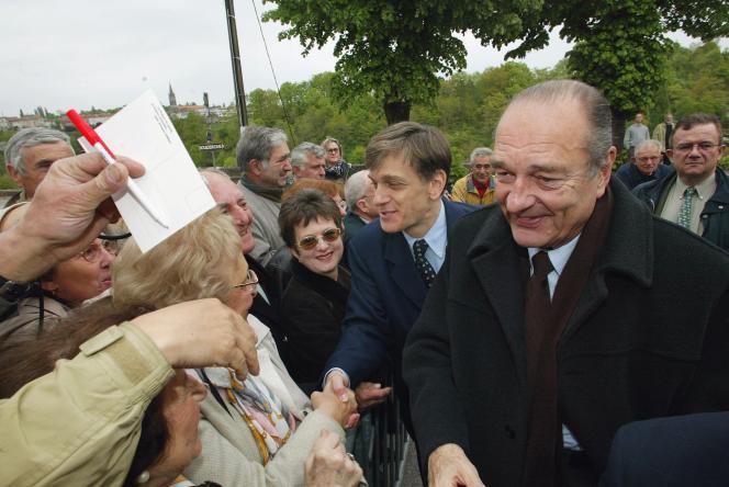 Le président candidat Jacques Chirac prend un bain de foule, en compagnie de Frédéric de Saint-Sernin (à gauche), le 28 avril 2002, à Nontron, lors d'un déplacement de campagne en Dordogne.